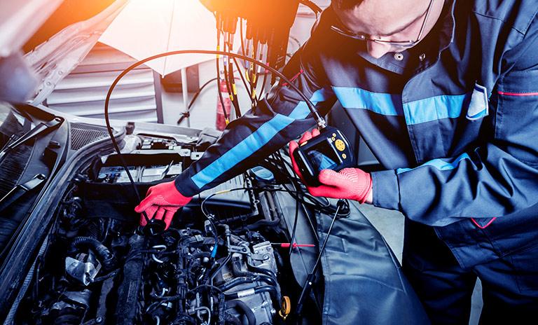 Mecánico realiza el mantenimiento de los carros eléctricos