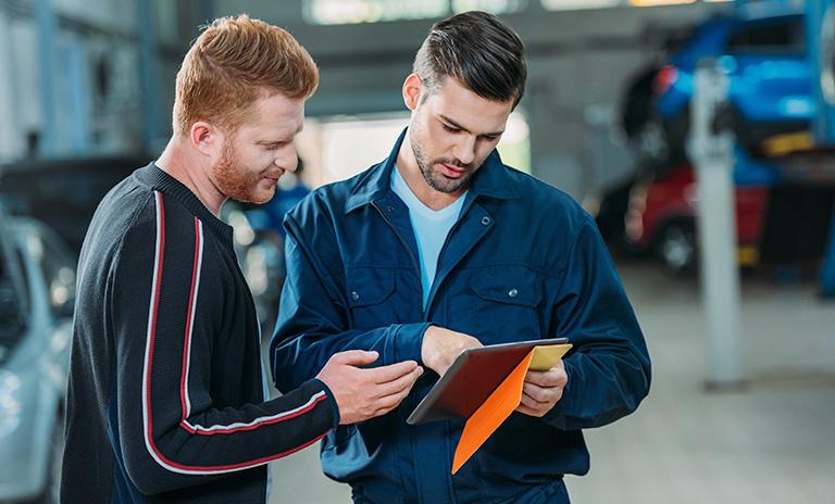 Técnico y cliente en la revisión tecnomecánica de los carros eléctricos